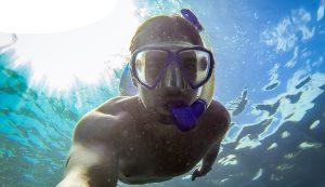 man met snorkel en duikbril op sterkte onder water