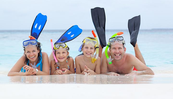 gezin met twee kinderen met duikuitrusting liggend op het strand
