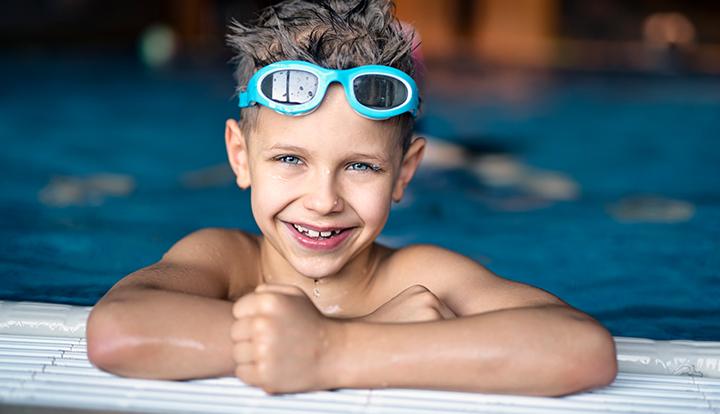 jongen in zwembad met zwembril op sterkte op zijn hoofd
