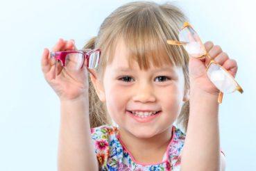 kind met brillen in haar hand