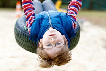 jongetje met bril op een schommel aan het spelen